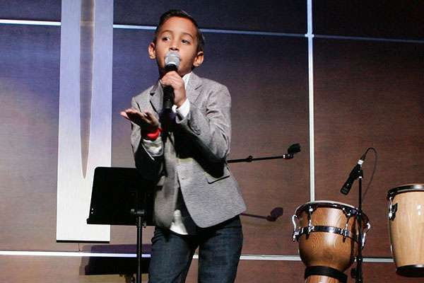 young boy singing on stage